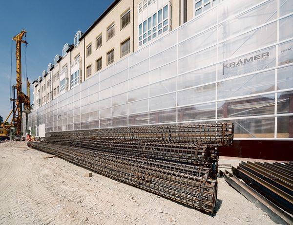Schall- und Staubschutz auf breiter Front: Im Zuge des Neubaus eines Tiefgaragen- und Geschäftshauskomplexes nahe der Münchener Altstadt sorgt die Krämer Gerüstbau GmbH aus Bockhorn für Staub- und Schallschutz. Hierzu kommt das Scaffguard-System von Scafom-rux zum Einsatz, das an freistehenden Ringscaff-Gerüstkonstruktionen befestigt wurde. Clou bei der wandernden Baustelle ist die komplette Versetzbarkeit von bis zu 11 m breiten Schutz-Elementen inklusive Stützgerüst. geruest.com
