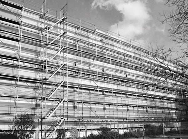 Durch das Anbringen einer Podesttreppe an einem Fassadengerüst können Handwerker deutlich schneller und sicherer im Gerüst auf- und absteigen als mit einem integrierten Leiternaufstieg und dabei mühelos Arbeitsmaterial und Werkzeug mitnehmen. geruest.com