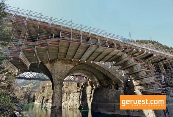 Ein 50 meter langes Hängegerüst konnte für eine Brückensanierung mit dem AllroundGerüst von Layher in Verbindung mit dem hochtragfähigen Ergänzungsbauteil FlexBeam realisiert werden